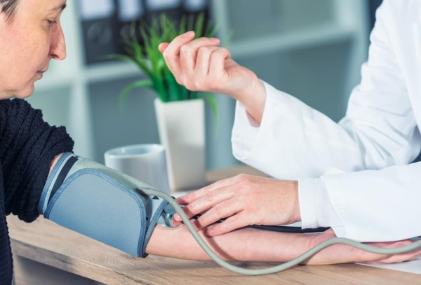 Doctor taking blood pressure of patient